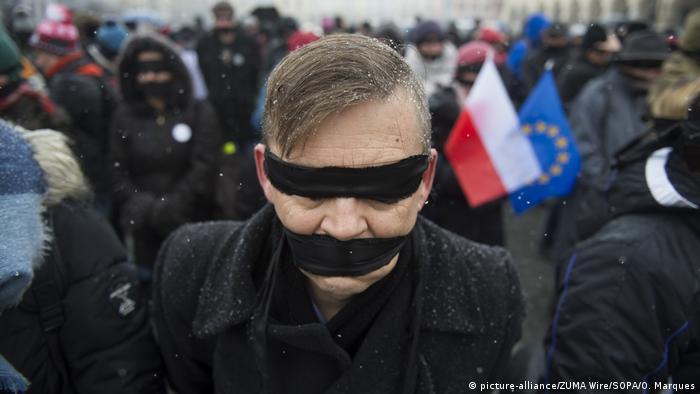 Ein Mann mit verbundenen Augen und verbundenem Mund bei der Veranstaltung Gestohlene Gerechtigkeit im polnischen Krakau am 21.01.2018 teil