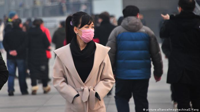 Tourists wearing face masks against air pollution visit the Bund along the Huangpu River in heavy smog in Shanghai, China