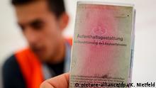 Der 20-jährige Saman aus der nordsyrischen Grenzstadt Kamischli ist am 27.07.2016 in Berlin bei der Flüchtlingshilfe Moabit hilft hinter seinem Asylbewerber-Ausweis zu sehen. Foto: Kay Nietfeld/dpa   Verwendung weltweit