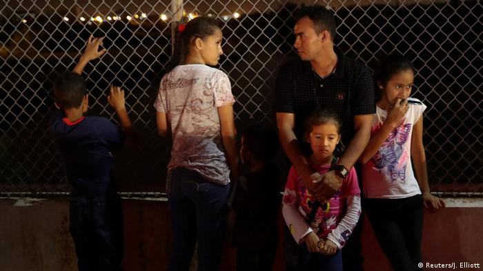 A family stands at a chainlink fence in the dark