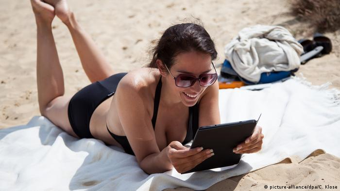 Woman at a beach with a tablet