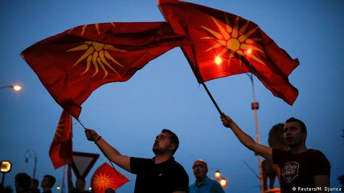 Люди размахивают флагами Македонии