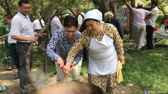 Lydia Rahnert (links), Ländermanagerin der DW Akademie für Kirgisistan, rührt mit im Plow. Das gemeinsame Kochen ist für die Journalisten ein Weg, auch mit der Bevölkerung in der Region ins Gespräch zu kommen. (DW/L. Rahnert)
