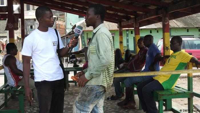 DW correspondent Maxwell Suuk interviewing another man