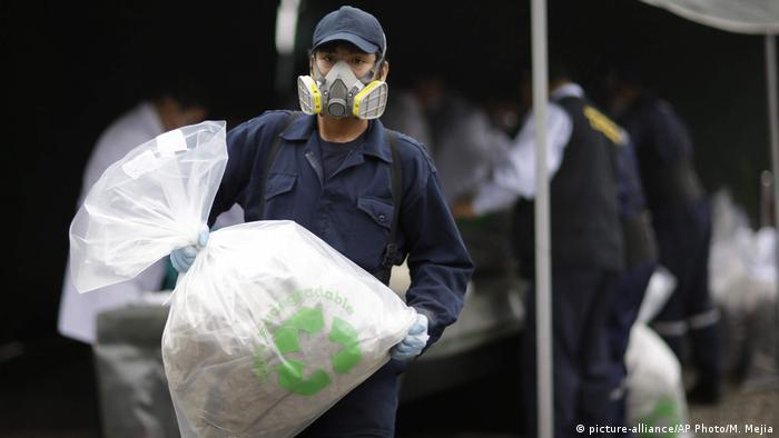 A Peruvian city employee carries a bag of seized cocaine