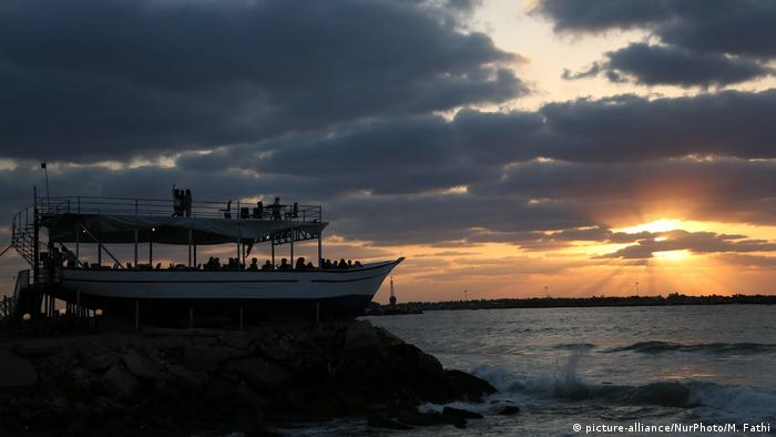 Palestinians dine at a beached boat by the coast near the Gaza City