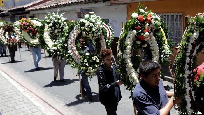 Mourners carry wreaths down a street (Reuers/I. Medina)