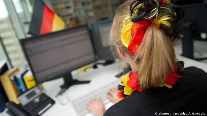 A woman wears German colours while working (picture-alliance/dpa/A. Warnecke)