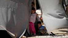 DARAA, SYRIA - AUGUST 17 : Syrian kids look out from a tent as many Syrian families forced to live due to the ongoing civil war in Daraa, Syria on August 17, 2017. Ammar Al Ali / Anadolu Agency  