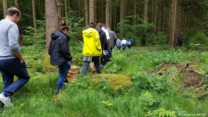 Foto: Eine Gruppe Menschen läuft durch den Wald (Quelle: Katharina Wecker)