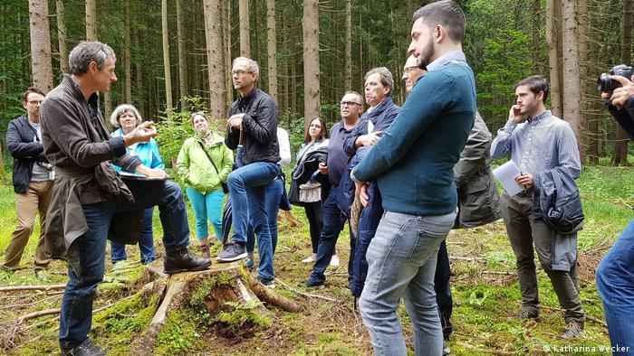 Foto; Rainer Kant und eine Gruppe stehen mitten im Fichtenwald (Quelle: Katharina Wecker)