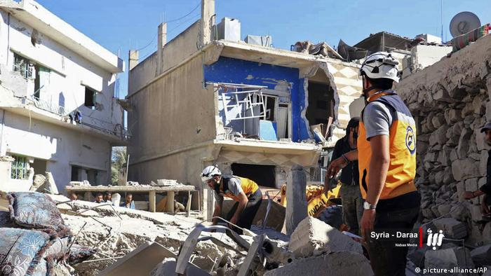 Civilians inspect damaged buildings in Daraa