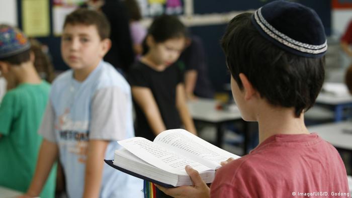 Ein jüdischer Schüler mit einem Gebetsbuch in der Schule