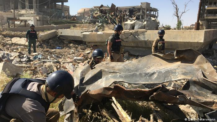 A team searches for unexploded devices amid rubble in Mosul