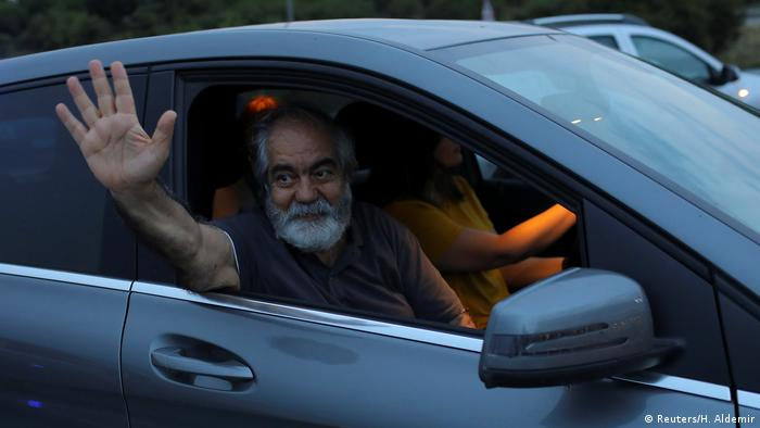 Writer and professor Mehmet Altan waves from a car after his release