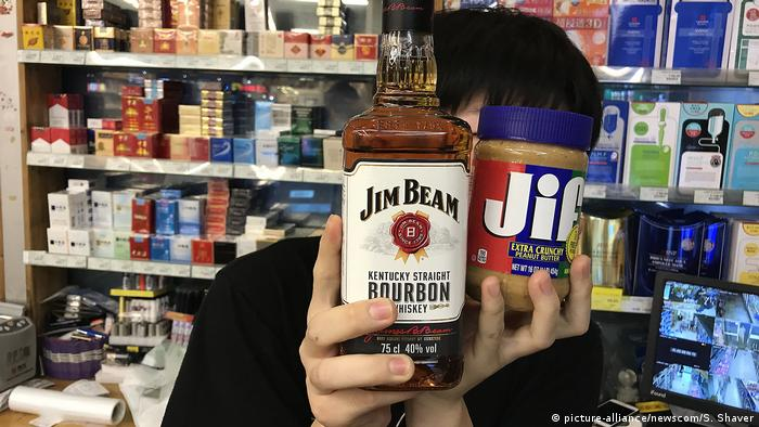 Bottle of whiskey and jar of peanut butter held by a cashier in a Beijing store (picture-alliance/newscom/S. Shaver)