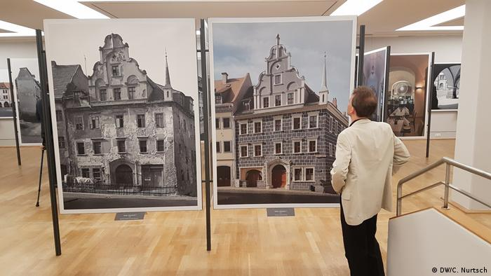 man stands in front of two large photos of a building (DW/C. Nurtsch)