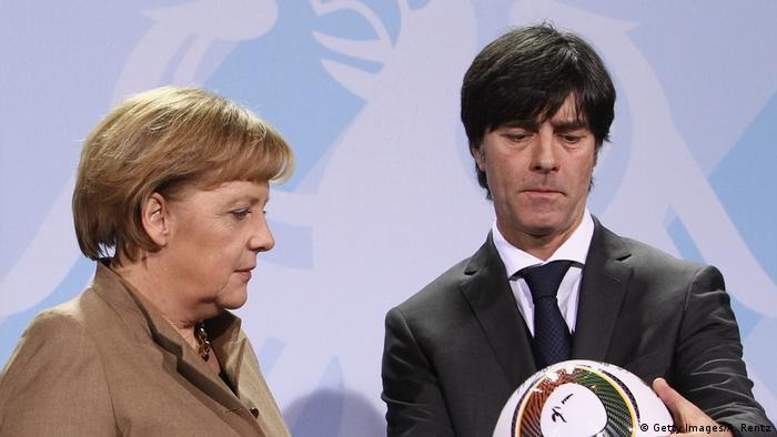 Angela Merkel and Jogi Löw looking at football (Getty Images/A. Rentz)