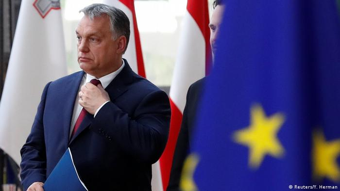 Orban adjusts his tie with a EU flag in the foreground