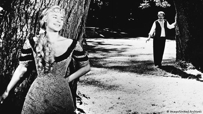 Film still Ingmar Bergman, Smiles of a summer Night, woman leaning on tree, man in the background (Imago/United Archives)