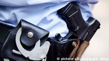 ARCHIV - 28.06.2011, Nordrhein-Westfalen, Köln: Ein Polizist mit Handschellen und Pistole am Gürtel steht in Köln. (zu dpa: Debatte über geplantes Polizeigesetz) Foto: Oliver Berg/dpa +++(c) dpa - Bildfunk+++ | Verwendung weltweit