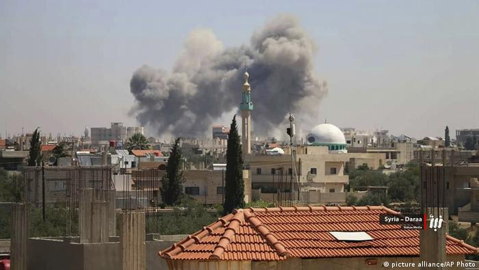 Smoke rises above the city of Deraa after a barrage of government airstrikes.