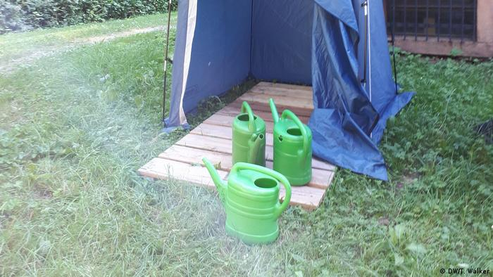 Watering cans in front of outdoor shower