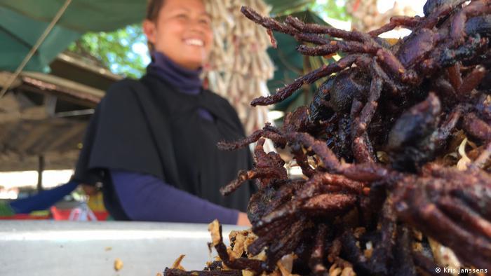 A women sells fried tarantula spiders in Skuon