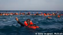 ARCHIV 24.05.2017 +++ LAMPEDUSA, ITALY - MAY 24: Refugees and migrants are seen swimming and yelling for assistance from crew members from the Migrant Offshore Aid Station (MOAS) 'Phoenix' vessel after a wooden boat bound for Italy carrying more than 500 people capsized on May 24, 2017 off Lampedusa, Italy. Numbers of refugees and migrants attempting the dangerous central Mediterranean crossing from Libya to Italy has risen since the same time last year with more than 43,000 people recorded so far in 2017. In an attempt to slow the flow of migrants Italy recently signed a deal with Libya, Chad and Niger outlining a plan to increase border controls and add new reception centers in the African nations, which are key transit points for migrants heading to Italy. MOAS is a Malta based NGO dedicated to providing professional search-and-rescue assistance to refugees and migrants in distress at sea. Since the start of the year MOAS have rescued and assisted 3572 people and are currently patrolling and running rescue operations in international waters off the coast of Libya. (Photo by Chris McGrath/Getty Images)