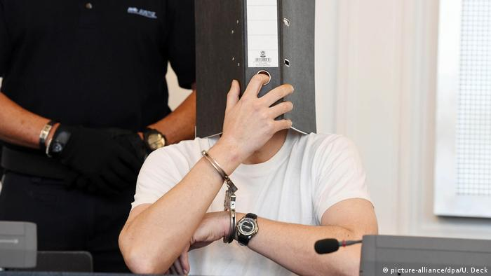 A man with handcuffs covers his face with a file in court