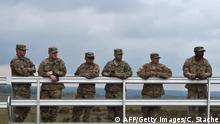 US soldiers stand at a visitor platform during the friendship shooting of the exercise 'Strong Europe Tank Challenge 2017' at the exercise area in Grafenwoehr, near Eschenbach, southern Germany, on May 12, 2017. Platoons from NATO nations France, Germany, USA and their partners Austria and Ukraine take part in this exercise. / AFP PHOTO / Christof STACHE (Photo credit should read CHRISTOF STACHE/AFP/Getty Images)
