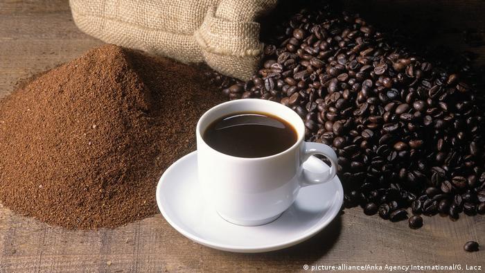 Taza de café, granos de café y café tostado