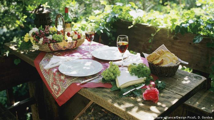 Gedeckter Holztisch im Freien mit Weintrauben, Brie-Käse, aufgeschnittenen Baguette und Wein (Foto: picture-alliance/Design Pics/L. D. Gordon)