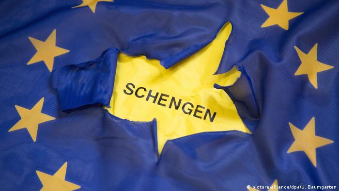 Zerrissene Europaflagge mit dem Schriftzug Schengen.