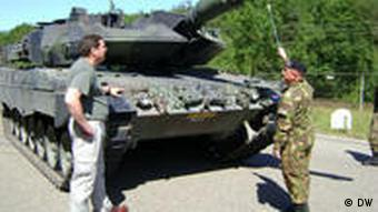 A Dutch sergeant points to a Leopard battle tank