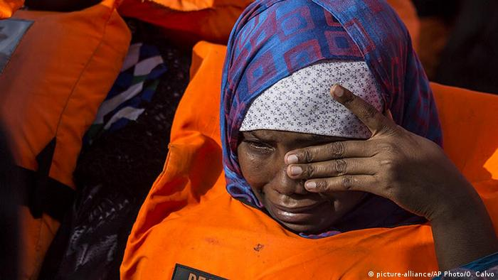 A woman wipes away tears as she and dozens of other migrants are rescued by the Open Arms, a ship operated by a Spanish NGO (picture-alliance/AP Photo/O. Calvo)