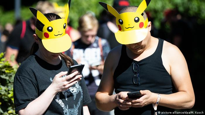 Two people wearing Pikachu visors take part in a Pokemon Go event in Dortmund, Germany