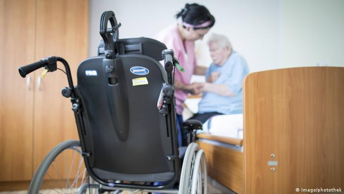 Болногледачка помага на възрастна жена да стане от леглото