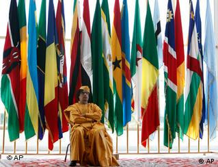 Gadhafi at sitting in front of flags at African Union summit