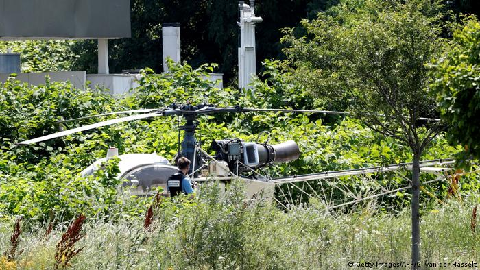 A forensic officer takes a photo of the helicopter abandoned by Redoine Faid after his escape from prison in Reau. (Getty Images/AFP/G. van der Hasselt)