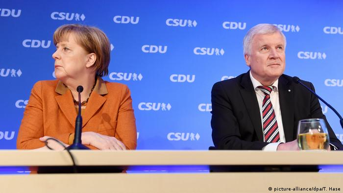 German Chancellor Angela Merkel sits next to CSU leader Horst Seehofer
