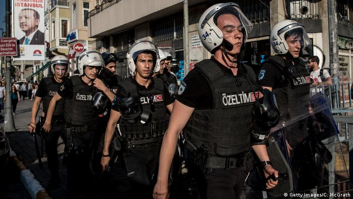 Riot police walk through an Istanbul street after dispersing LGBT supporters