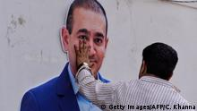 An Indian supporters of the Congress Party keeps his hand on the face of a cut out of billionaire jeweller Nirav Modi during a protest in New Delhi on February 16, 2018. Indian investigators on February 15 raided the premises of a billionaire jeweller accused of defrauding one of the country's biggest banks. Enforcement Directorate (ED) officers searched the Mumbai offices of Nirav Modi after he was accused of cheating state-owned Punjab National Bank (PNB) of 2.8 billion rupees ($43.8 million). / AFP PHOTO / CHANDAN KHANNA (Photo credit should read CHANDAN KHANNA/AFP/Getty Images)