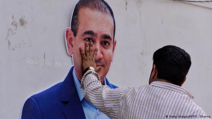 A man puts his hand on a photo of billionaire jeweler Nirav Modi in New Delhi