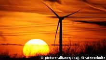ARCHIV - 04.02.2010, Rheinland-Pfalz, Pfalzfeld. Die Silhouetten eines Windrades und einer Hochspannungsleitung zeichnen sich am 04.02.2010 in der Nähe von Pfalzfeld (Rhein-Hunsrück-Kreis) vor einem farbenprächtigen Himmel neben der untergehenden Sonne ab. (zu dpa Erstmals mehr als 100 Milliarden Kilowattstunden Ökostrom im Halbjahr am 02.07.2018) Foto: Julian Stratenschulte/dpa +++ dpa-Bildfunk +++   Verwendung weltweit