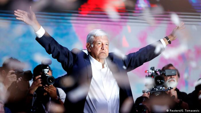 AMLO holds out his arms as cameras take photos of him and confetti falls