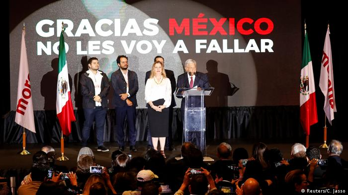 AMLO speaks on stage surrounded by his wife and team