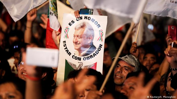 A supporter of AMLO holds up a sign with his face on it