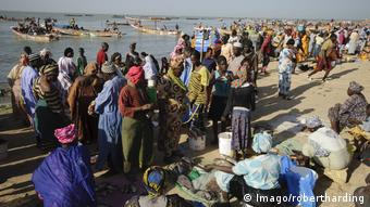 Fishmongers and customers congregate on the beach, with fishing canoes in the waters behind them
