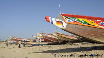 A row of colorful wooden fishing canoes docked on the beach.